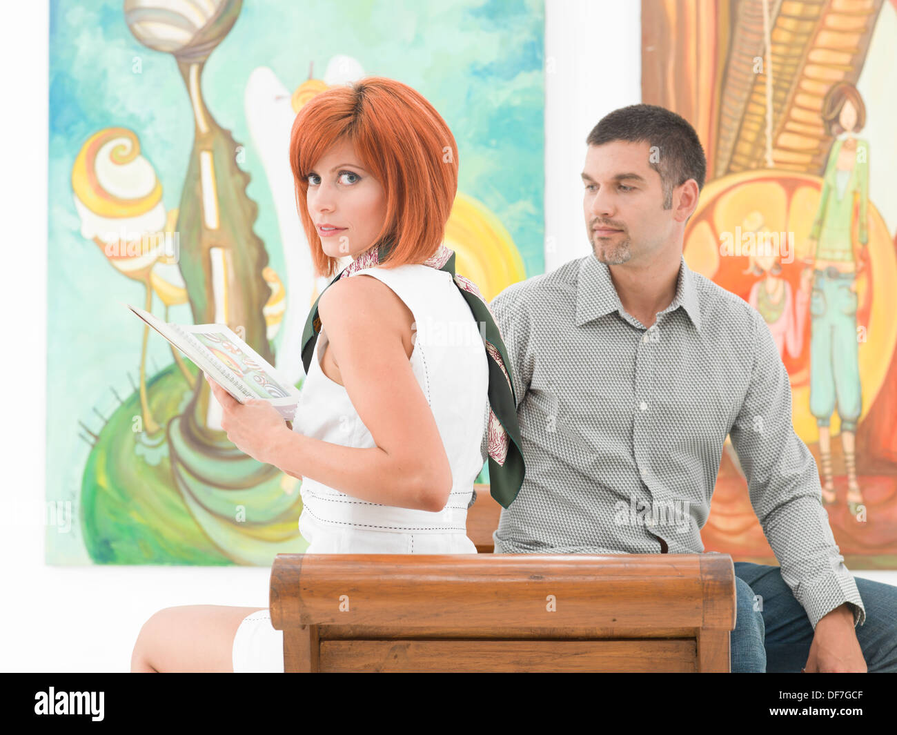 close-up of young caucasian man sitting on a wooden bench next to a beautiful redhead woman, with colorful artworks on background - Stock Image