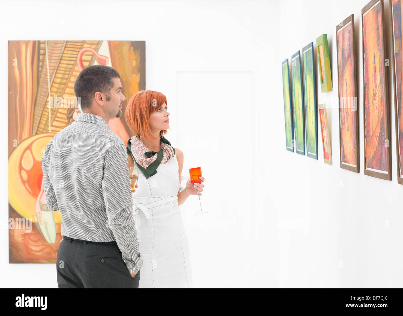 young caucasian couple standing in a gallery and holding colorful glasses of wine in their hands, contemplating artwork displayed on walls - Stock Image