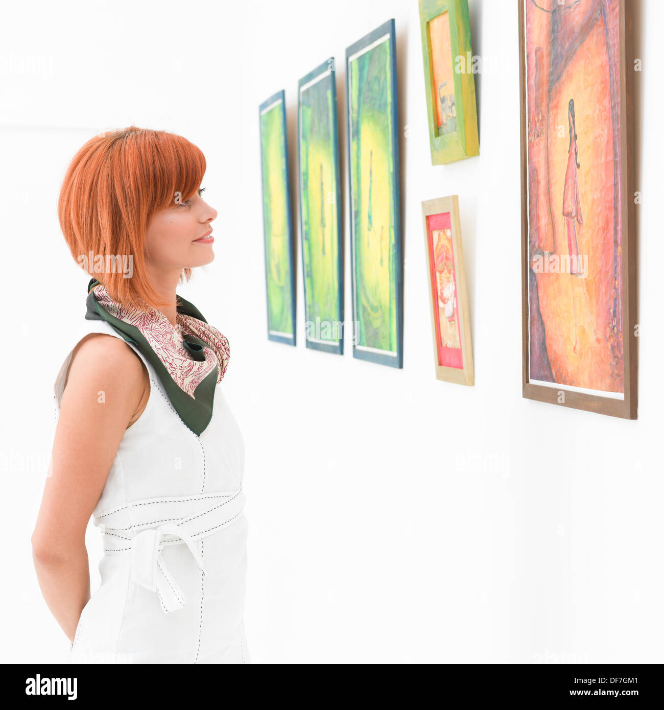 side view of young attractive redhead woman standing in an art gallery contemplating an artwork - Stock Image