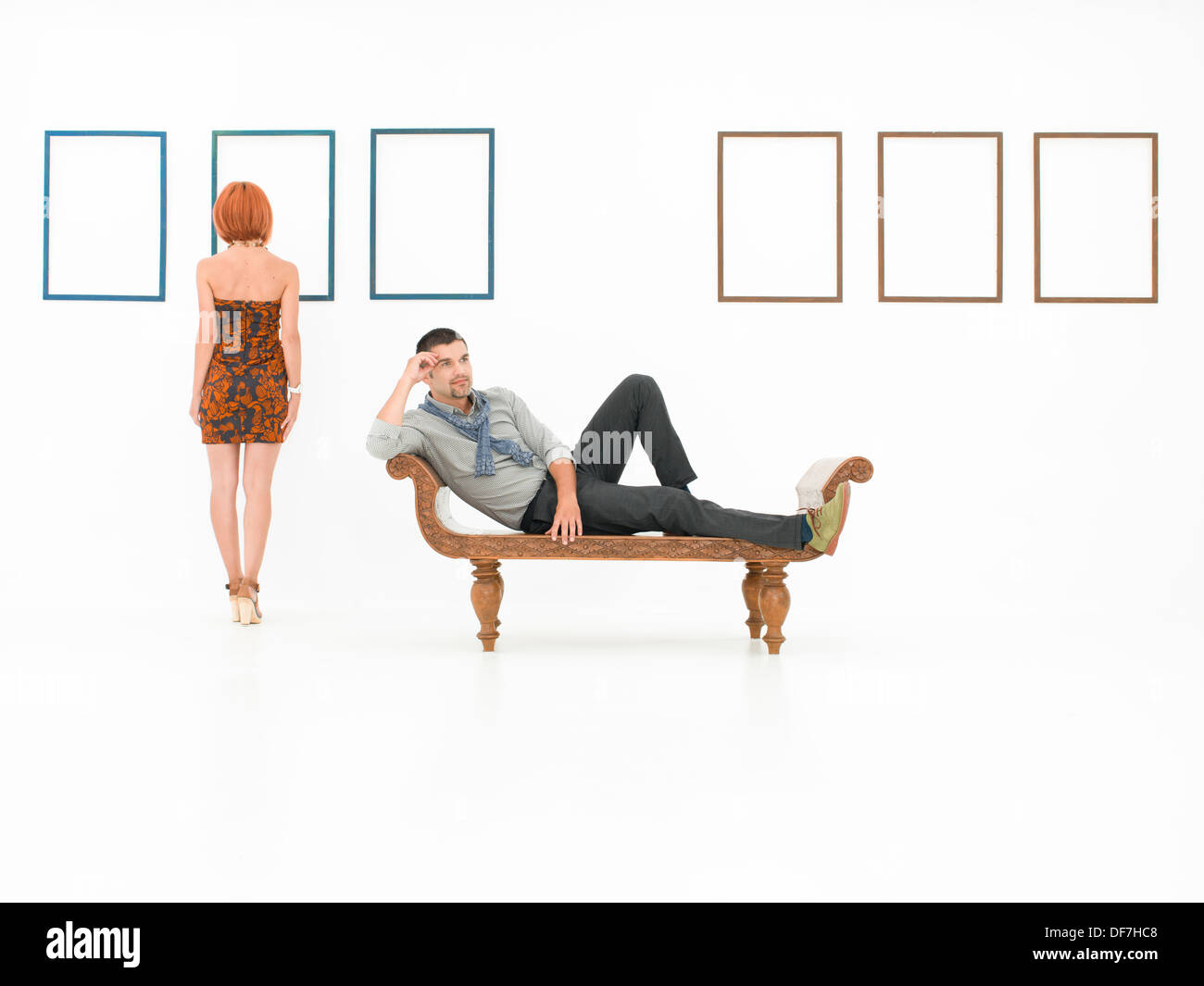 two young caucasian people in a white room with empty frames displayed on walls - Stock Image