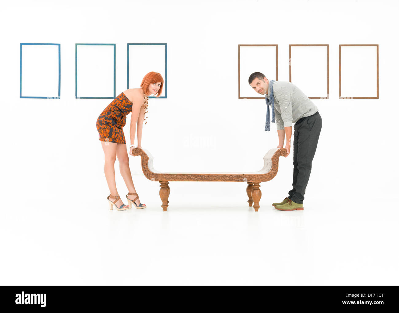 two caucasian people trying to lift up a wooden bench in a white room with empty frames displayed on walls - Stock Image