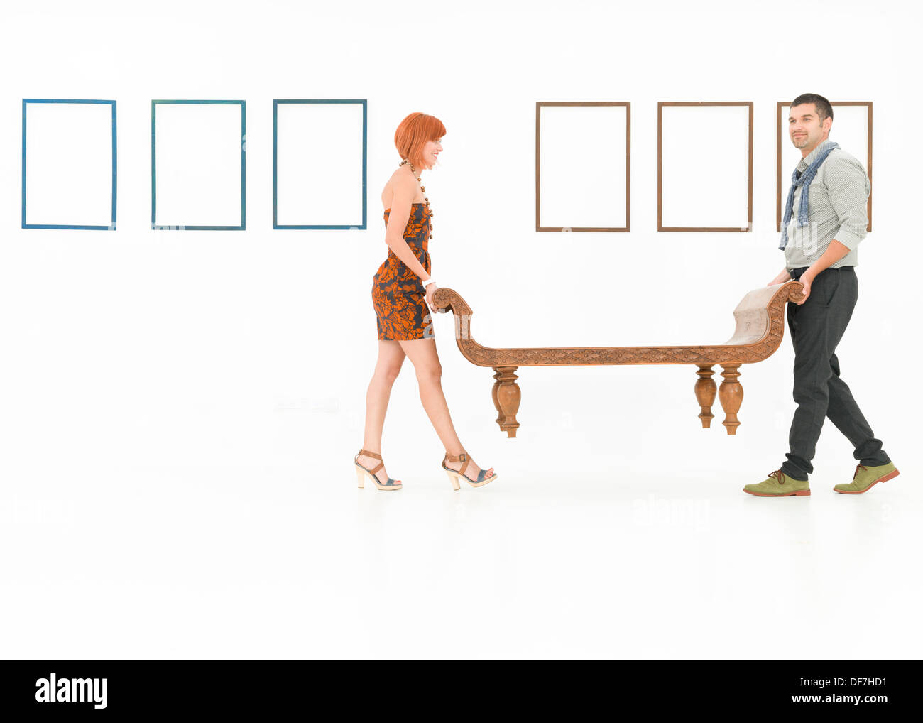 two caucasian people carrying a wooden bench in a white room with empty frames displayed on walls - Stock Image