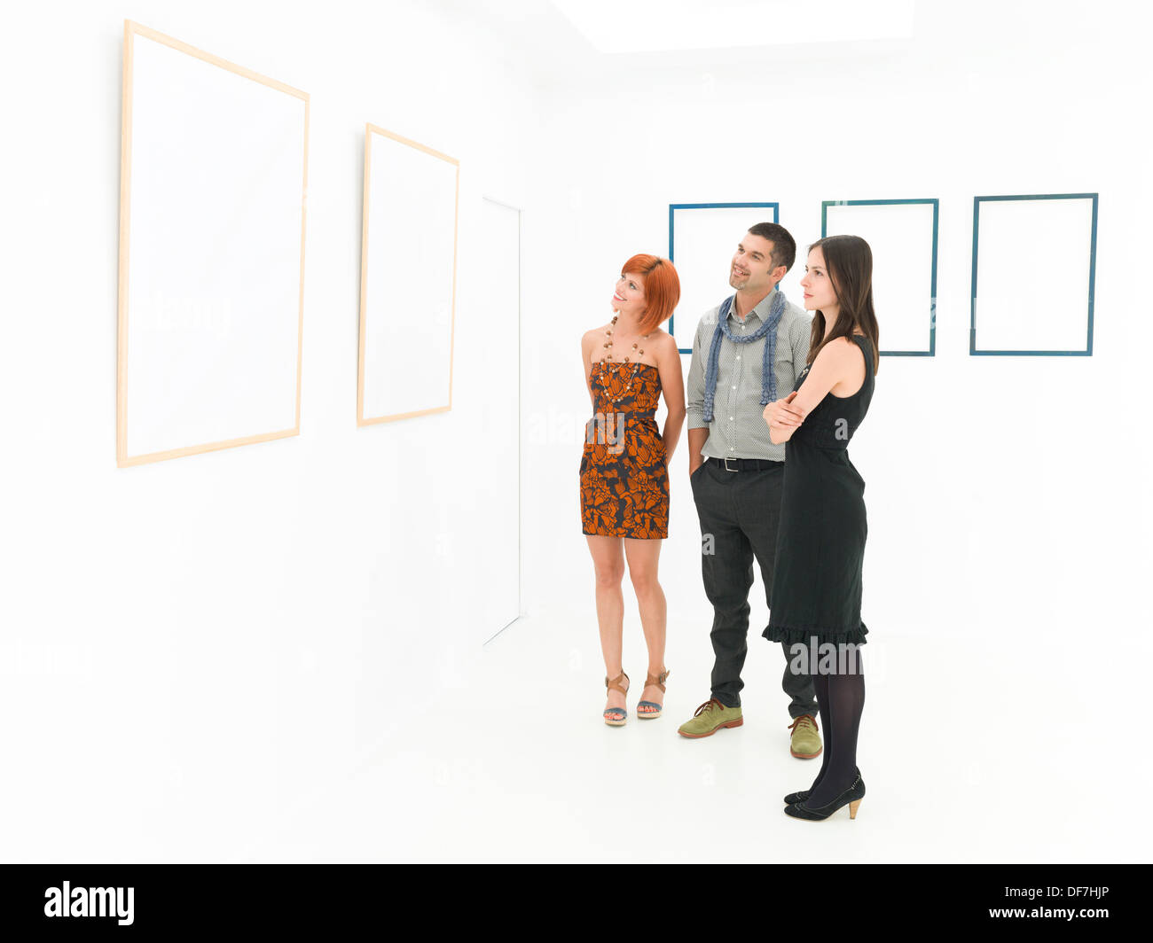 group of young caucasian people standing in front of large empty frames displayed on white walls, contemplating them - Stock Image