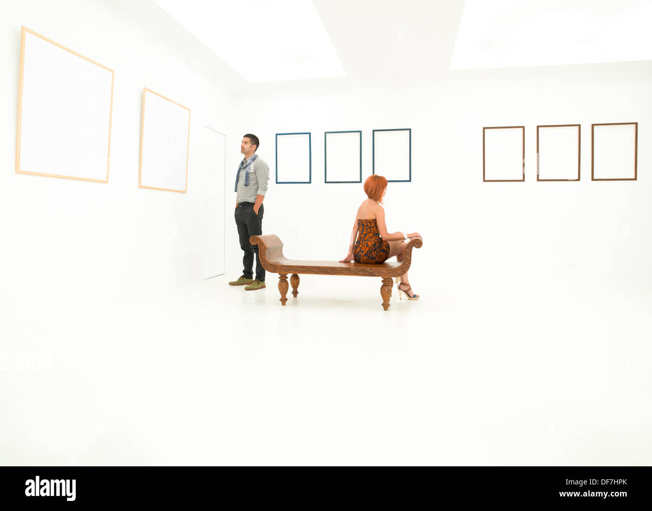 woman and man contemplating empty frames displayed on white walls - Stock Image