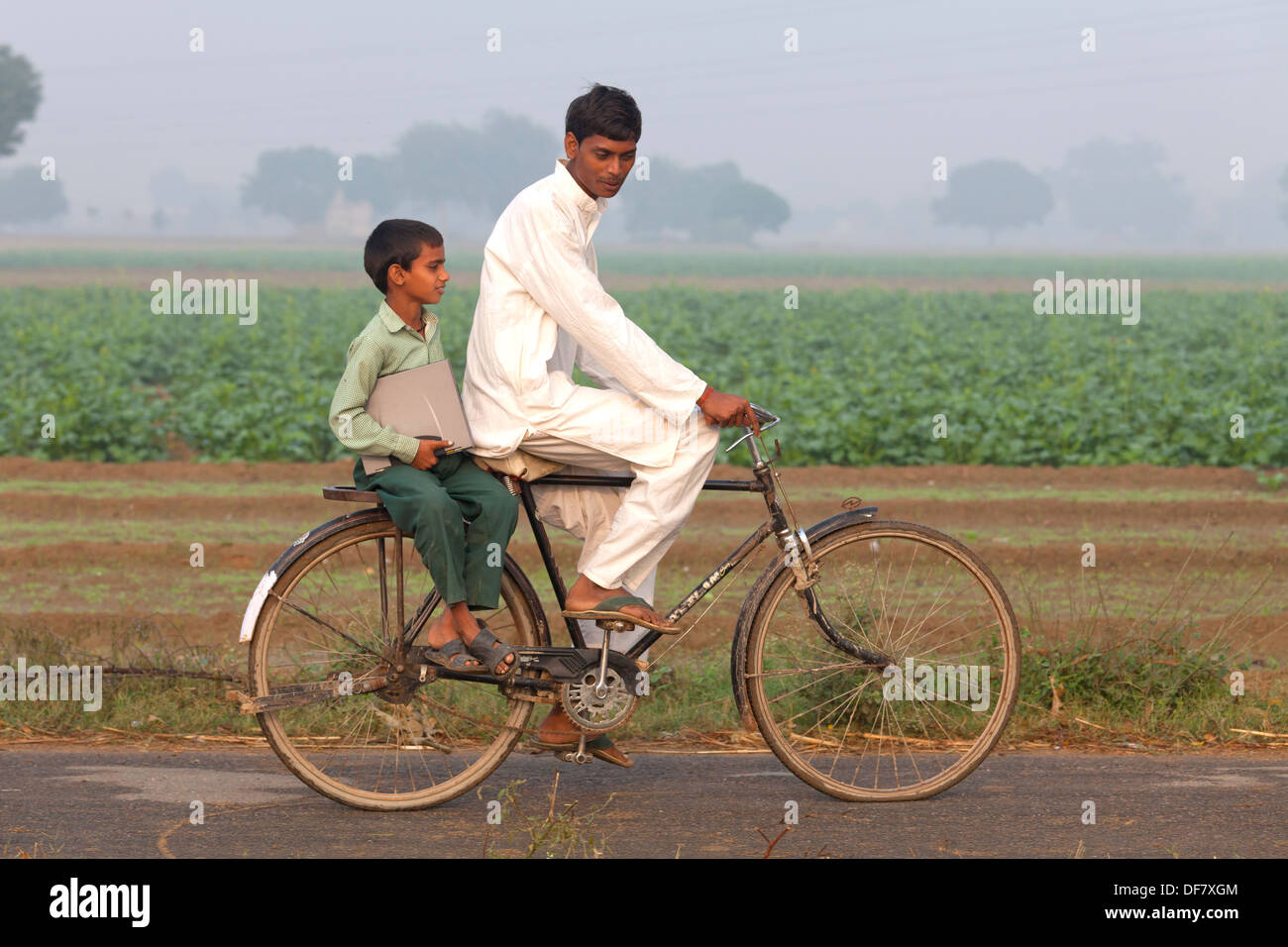 1e2b12b398f india, Uttar Pradesh, young male riding bike with younger boy in school  uniform on
