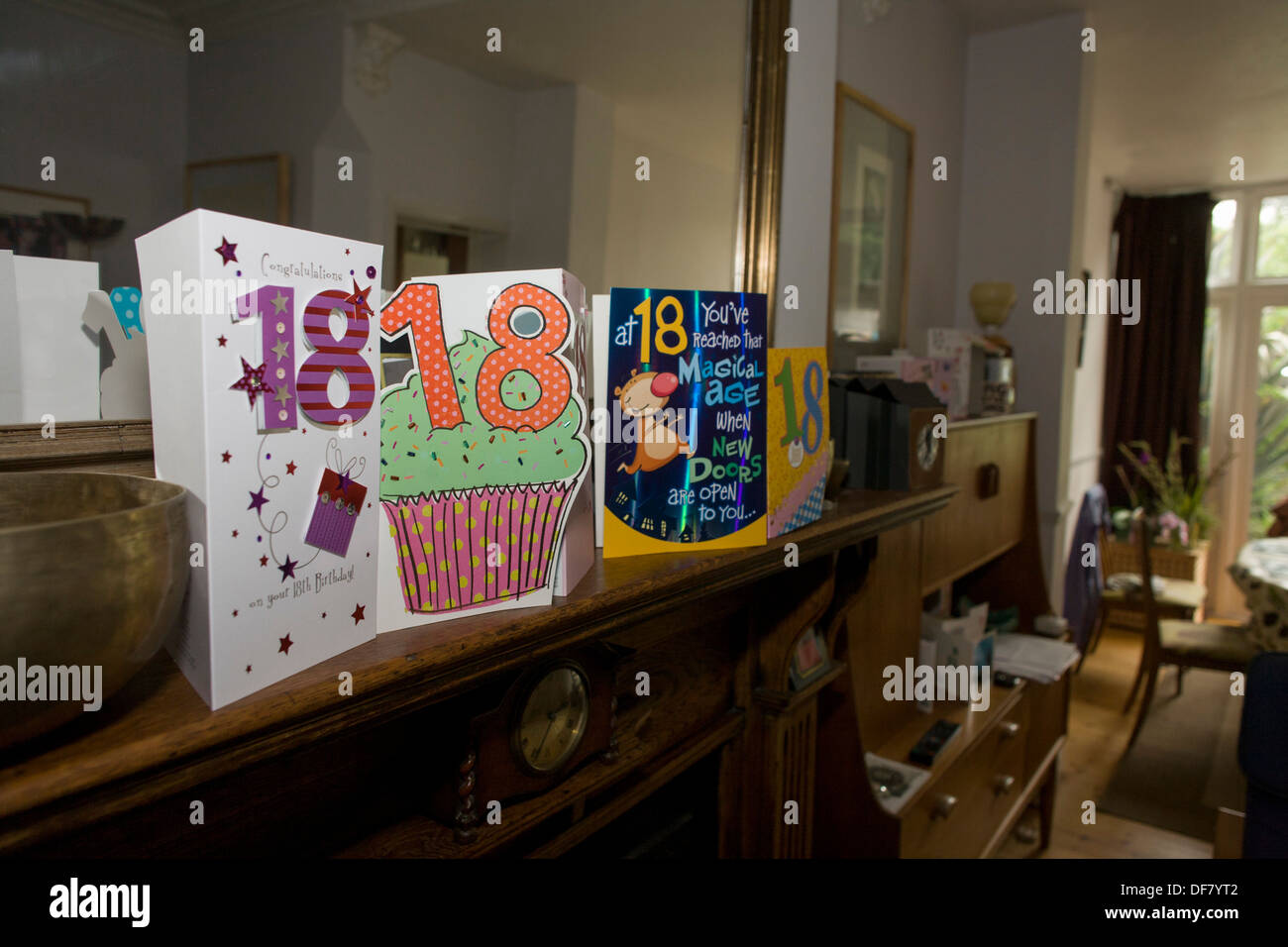 18th birthday cards mark the rite of passage, from childhood to adulthood, on a living room mantlepiece. - Stock Image