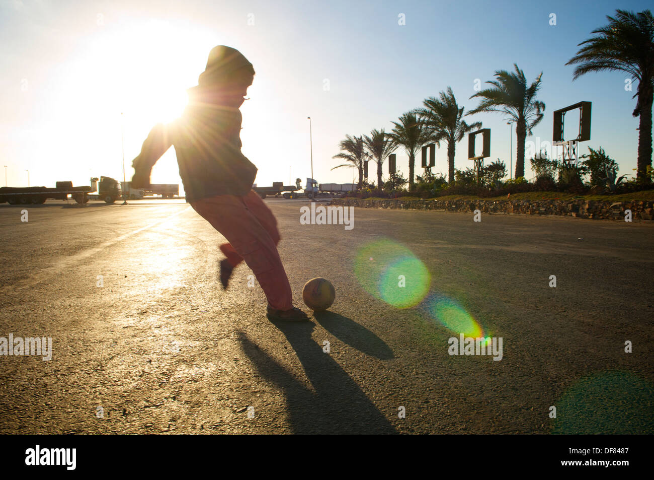 Young Egyptian man playing football at a gas stop in the Eastern Desert - Stock Image