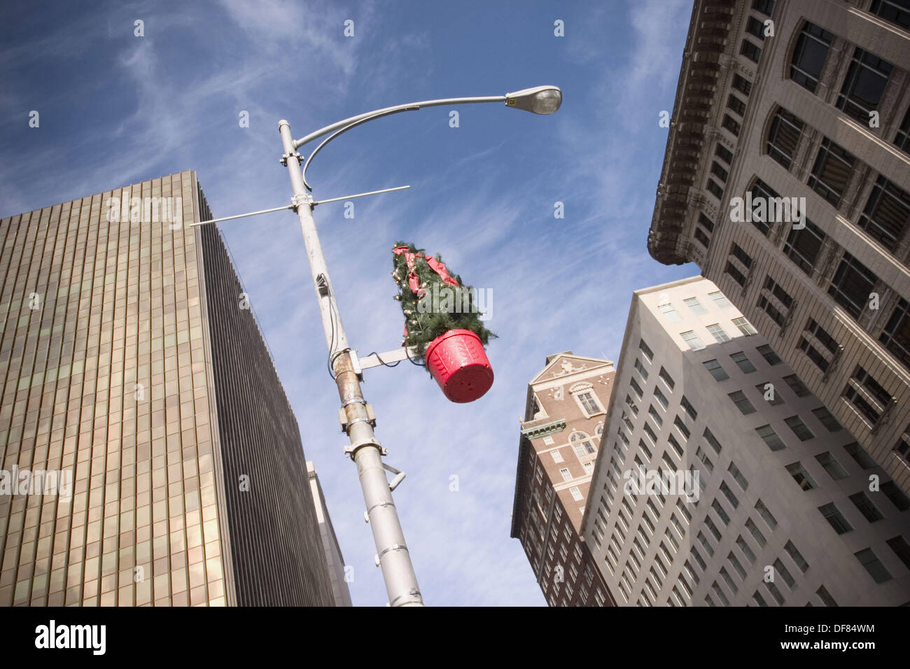 christmas decorations attached to a light pole on a city street stock image