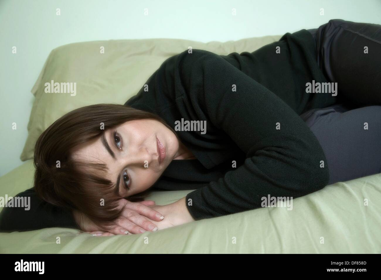 Young woman lying on her bed - Stock Image