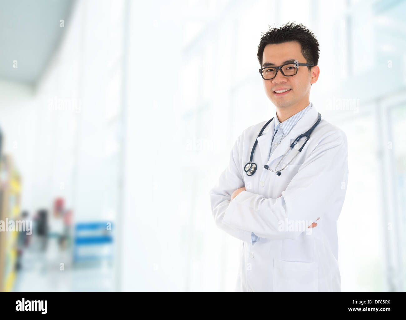 Asian male medical doctor with confident smile standing inside hospital building. - Stock Image