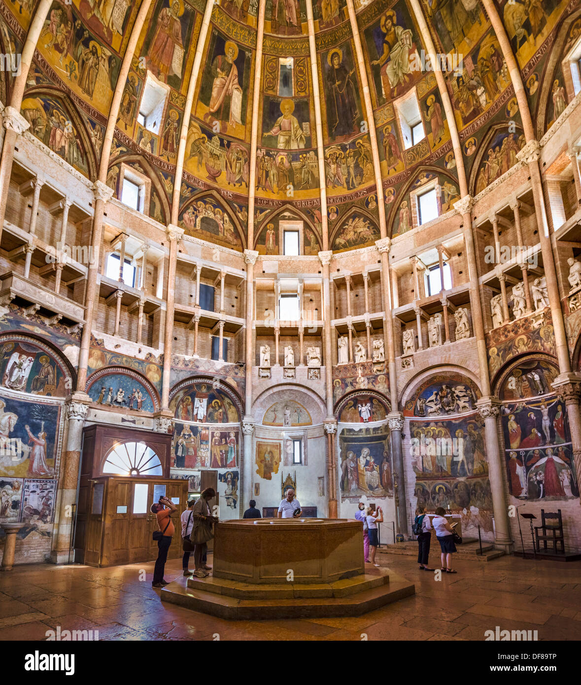 Tourists inside the historic medieval Baptistery, Parma, Emilia Romagna, Italy - Stock Image