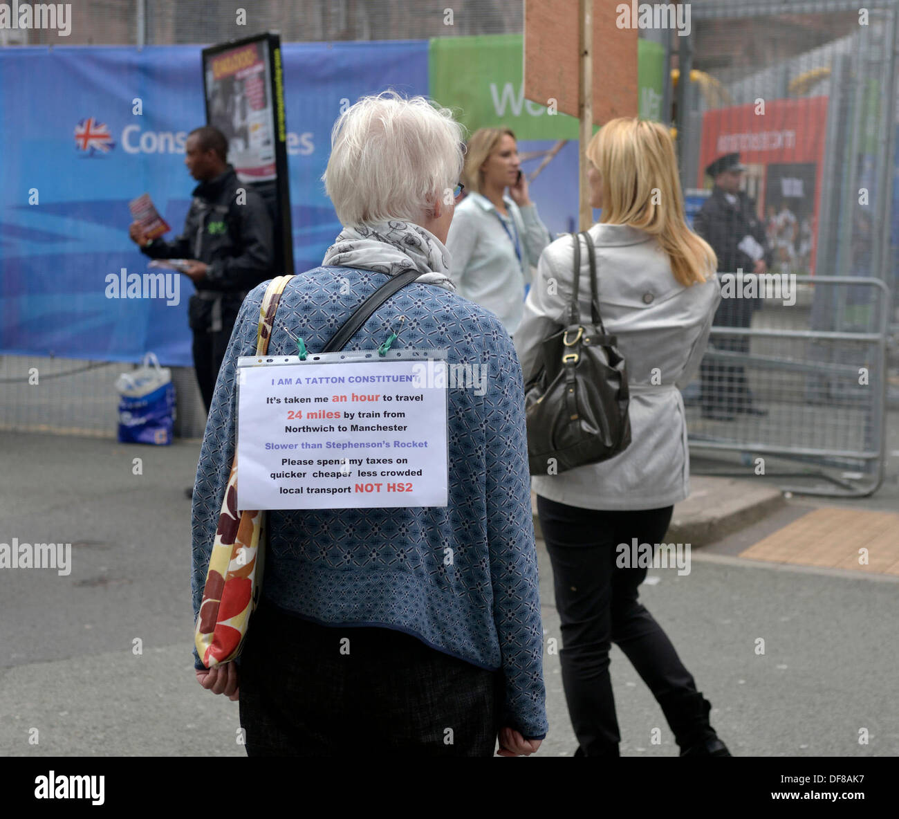 Manchester, UK . 30th Sep, 2013. A middle-aged woman has a notice on her back protesting against HS2 outside the Conservative Party Conference in Manchester. Conservative Party Conference Manchester, UK 30 September 2013 Credit:  John Fryer/Alamy Live News - Stock Image