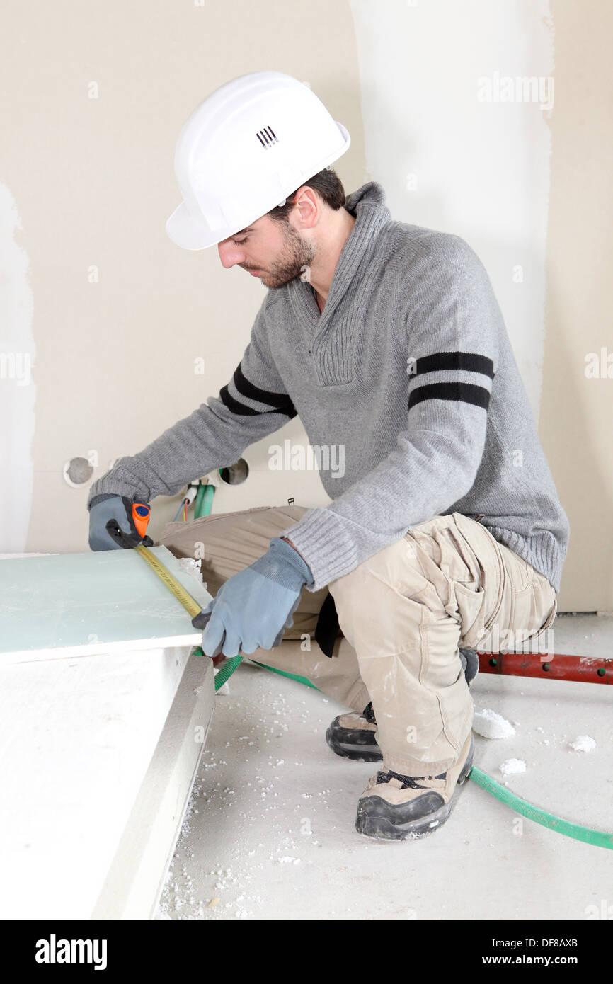 Worker measuring plasterboard Stock Photo