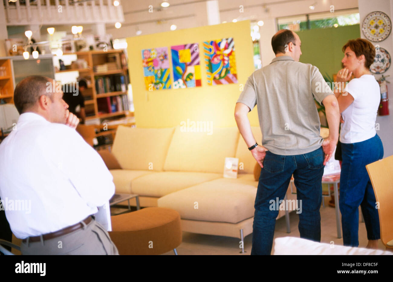 Couple And Salesman In A Furniture Store