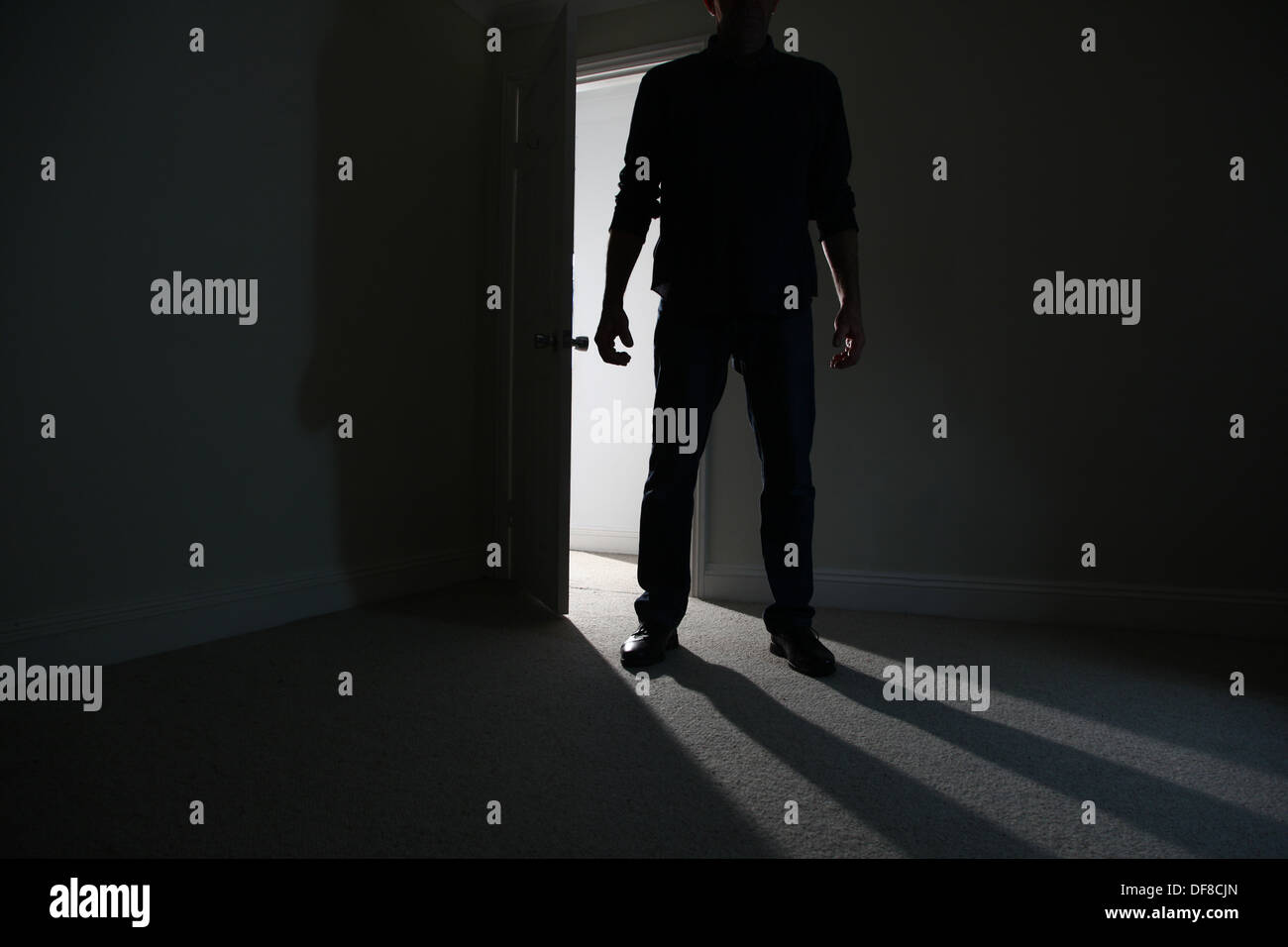 Silhouette of a male adult standing in an open doorway, entering a dark room. Model released - Stock Image