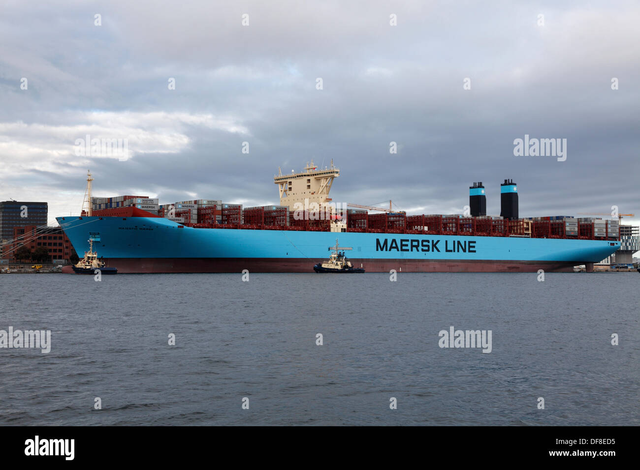 Copenhagen, Denmark. 30th Sep, 2013. The Majestic Maersk left the Langelinie quay in Copenhagen after one week's official naming ceremony and presentation to Maersk relations and the Danish public. Majestic Maersk, now heading for Gothenburg in Sweden to enter the container service between Europe and Asia, will probably never visit Copenhagen again as it is off-route and not suitable for this size of ship. By help of own propellers and four Svitzer tugs the ship was backed out of the harbour, as it is too shallow and small for a triple-E class ship to turn. Credit:  Niels Quist/Alamy Live News - Stock Image