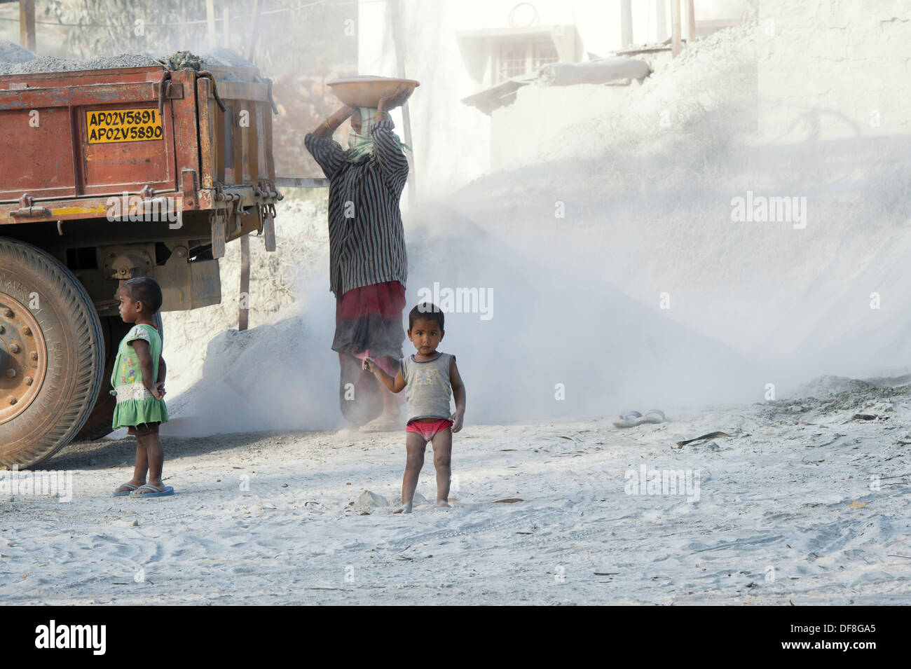 Indian children playing, surrounded by dust, unprotected, at a stone crushing works. Andhra Pradesh, India - Stock Image