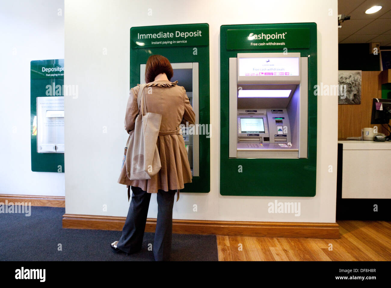 A customer using the new Immediate Deposit facilty, interior of Lloyds Bank, Concept of Modern Technology in Banks, UK - Stock Image