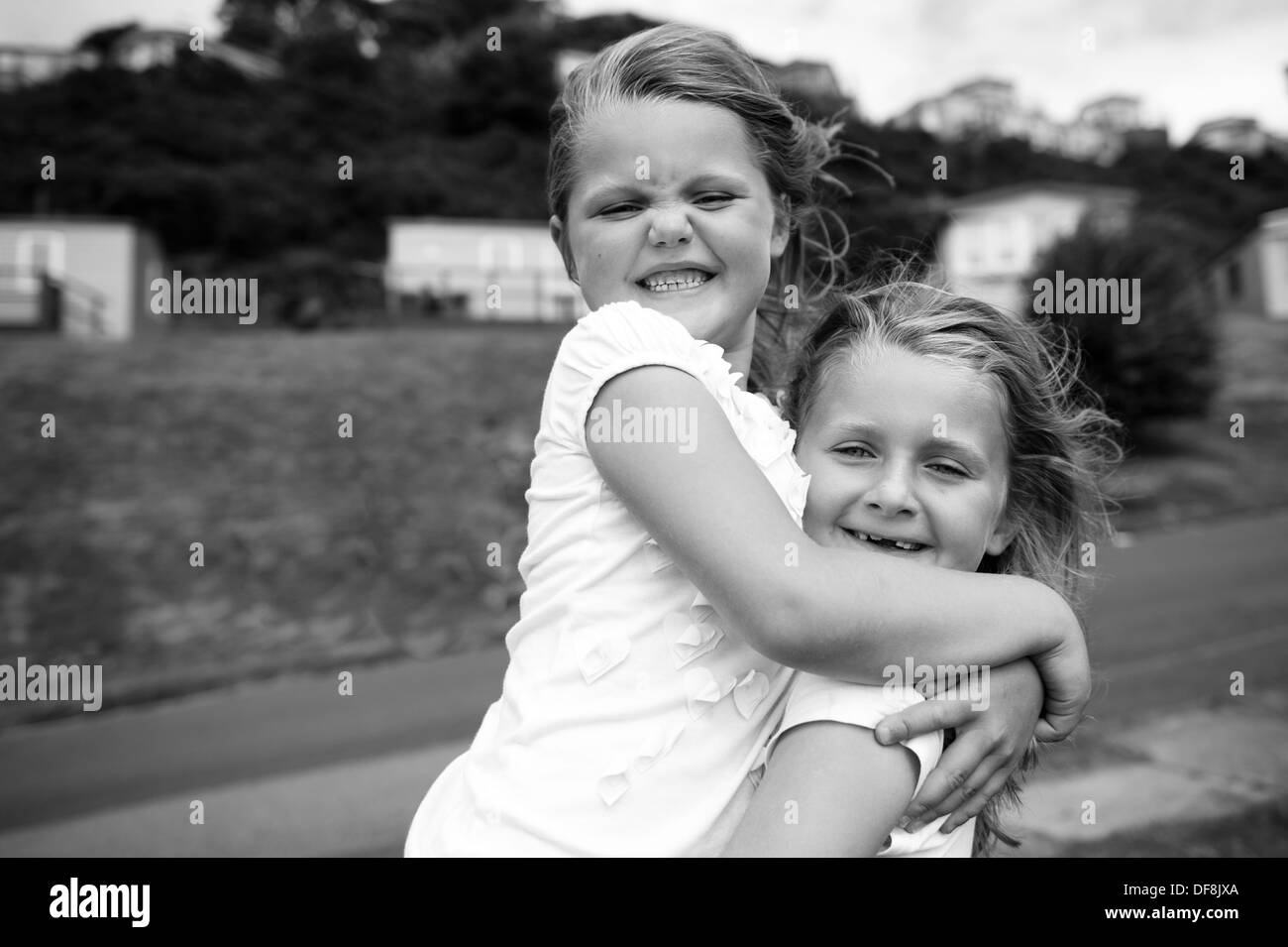 girls with toothy grins hugging black and white - Stock Image