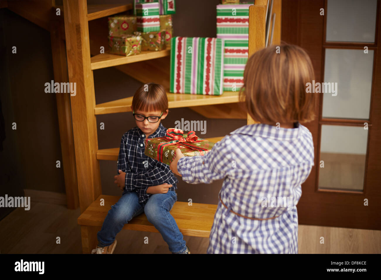 Spoiled kid refusing a Christmas present his sister is offering - Stock Image