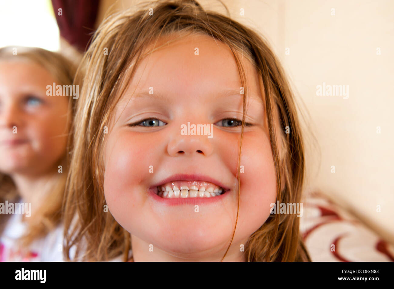 girl smiling to camera with toothy grin and sister in background - Stock Image