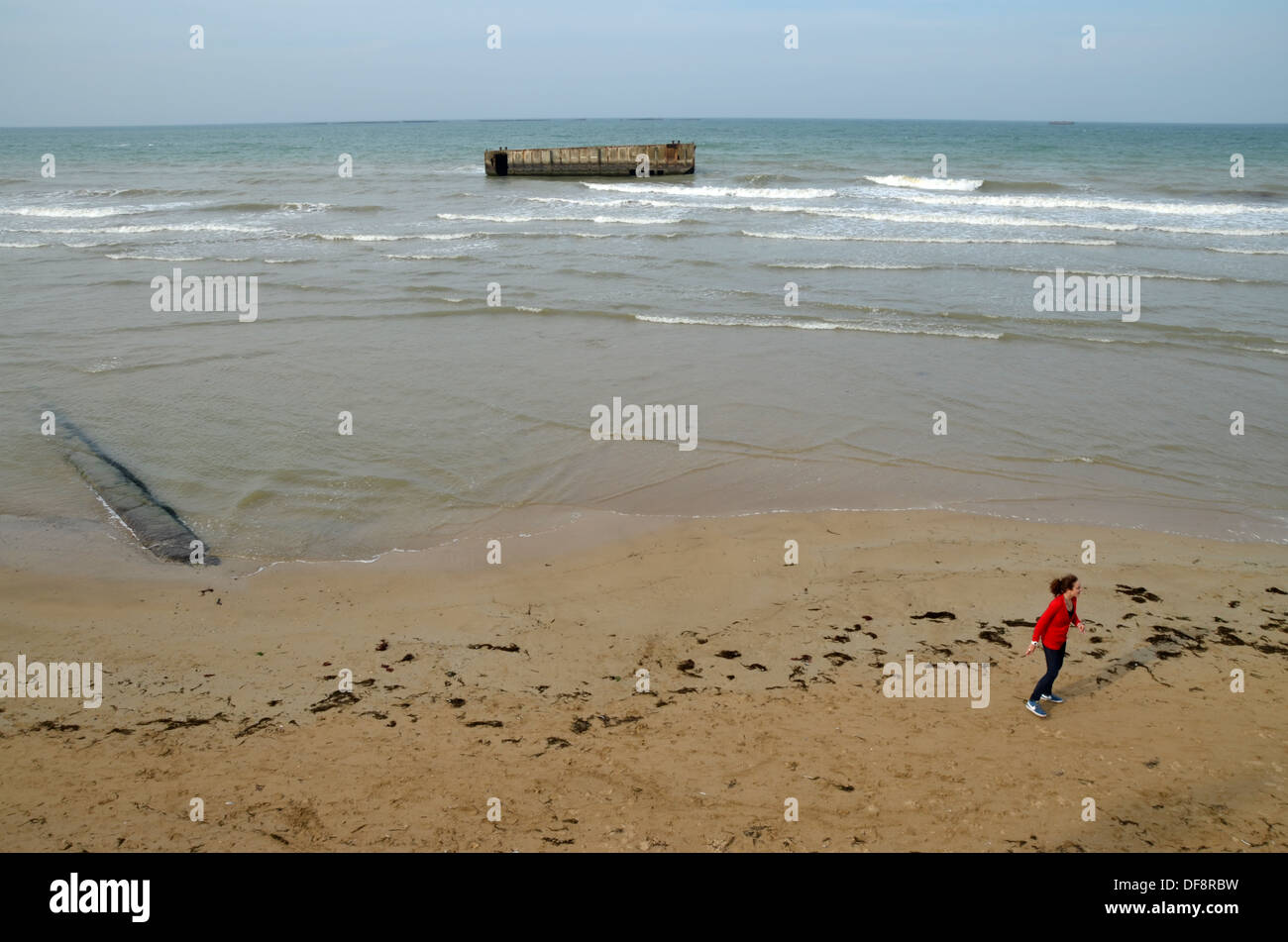 1944 D-day in Normandy: french youngster before the remains of the Mulberry harbour in Arromanches, Normandy. - Stock Image