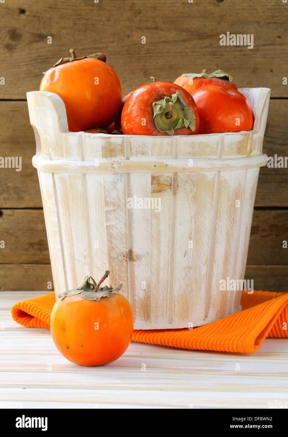 Orange ripe persimmon in a wooden bucket - Stock Image