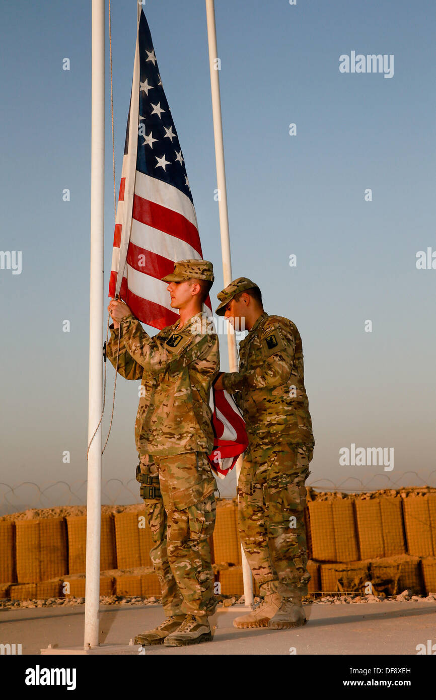 Tarin Kot, Afghanistan. 29th Sep, 2013. United States Army Spcs. Michael Arsenault and Jesus Arias lower the flags of the Camp Holland memorial for the final time September 29, 2013 in Tarin Kot, Afghanistan. As American forces continue to draw down forces in Afghanistan the camp will be handed over to Afghan Forces. © Planetpix/Alamy Live News - Stock Image
