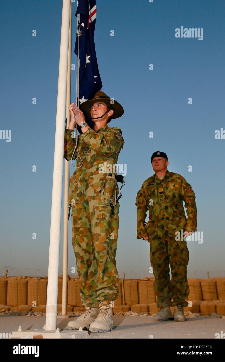 Tarin Kot, Afghanistan. 29th Sep, 2013. Royal Australian Air Force Warrant Officer Jennine Riches and Sgt. Chris Cambell lower the Australian flag during a lower the flag ceremony of the Camp Holland memorial for the final time September 29, 2013 in Tarin Kot, Afghanistan. As ISAF forces continue to draw down in Afghanistan the camp will be handed over to Afghan Forces. © Planetpix/Alamy Live News - Stock Image