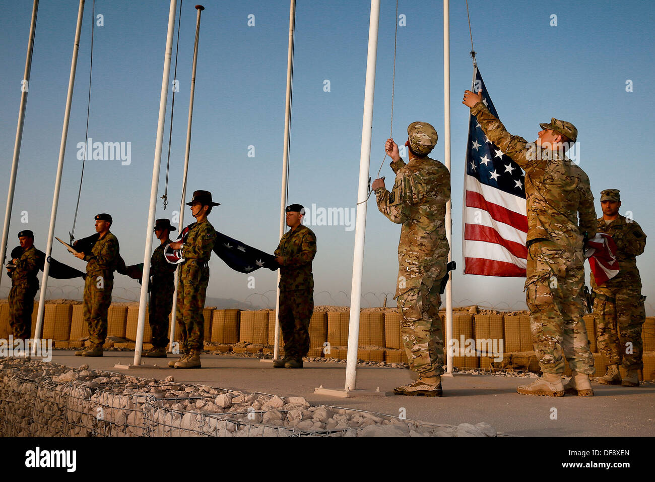 Tarin Kot, Afghanistan. 29th Sep, 2013. Australian and United States military personnel from Combined Team Uruzgan lower the flags of the Camp Holland memorial for the final time September 29, 2013 in Tarin Kot, Afghanistan. As American forces continue to draw down forces in Afghanistan the camp will be handed over to Afghan Forces. © Planetpix/Alamy Live News - Stock Image