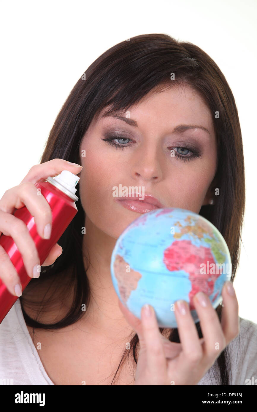 Woman spraying miniature globe - Stock Image