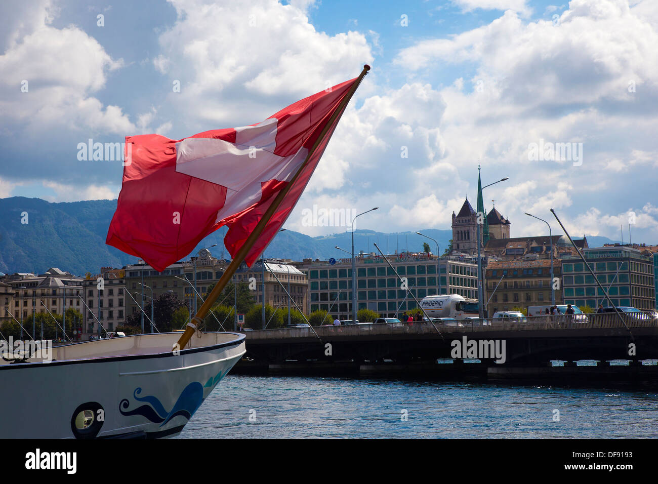 Swiss flag flying from a boat in Lake Geneva with the city in the background - Stock Image