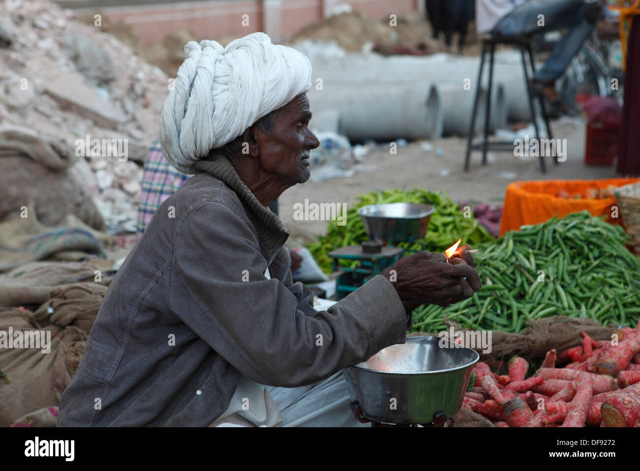 Old vegetable salesman lighting up a cigarette in a market in Jaipur, Rajasthan,India. - Stock Image