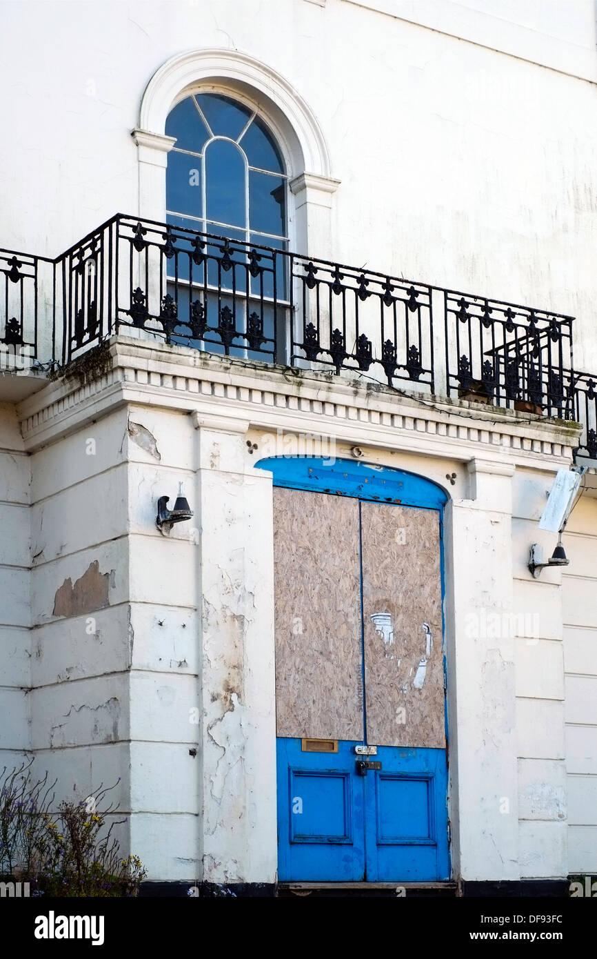 shabby derelict doorway with broken surveillance camera on an abandoned empty building - Stock Image