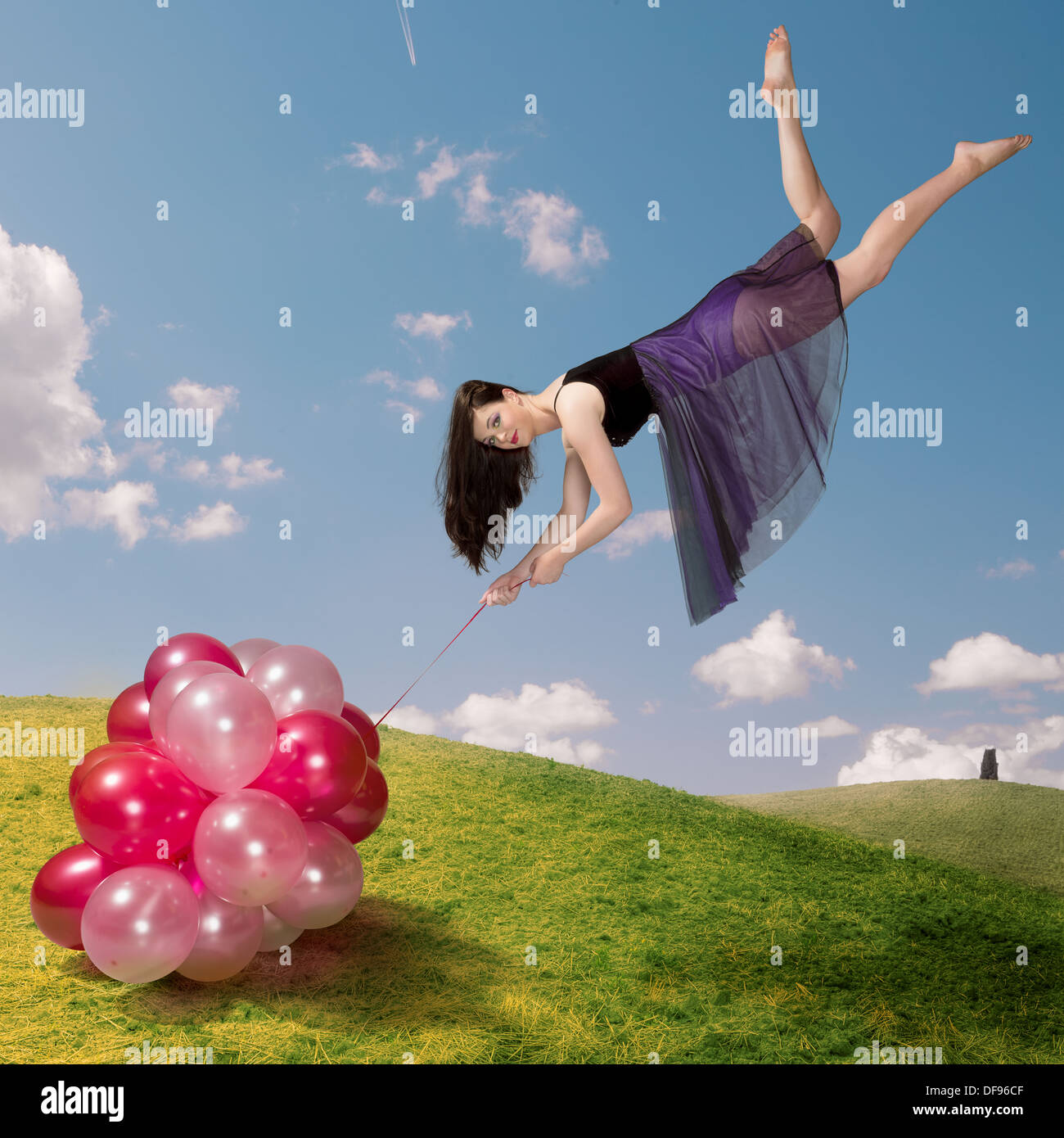 Flying girl holding colourful balloons Stock Photo