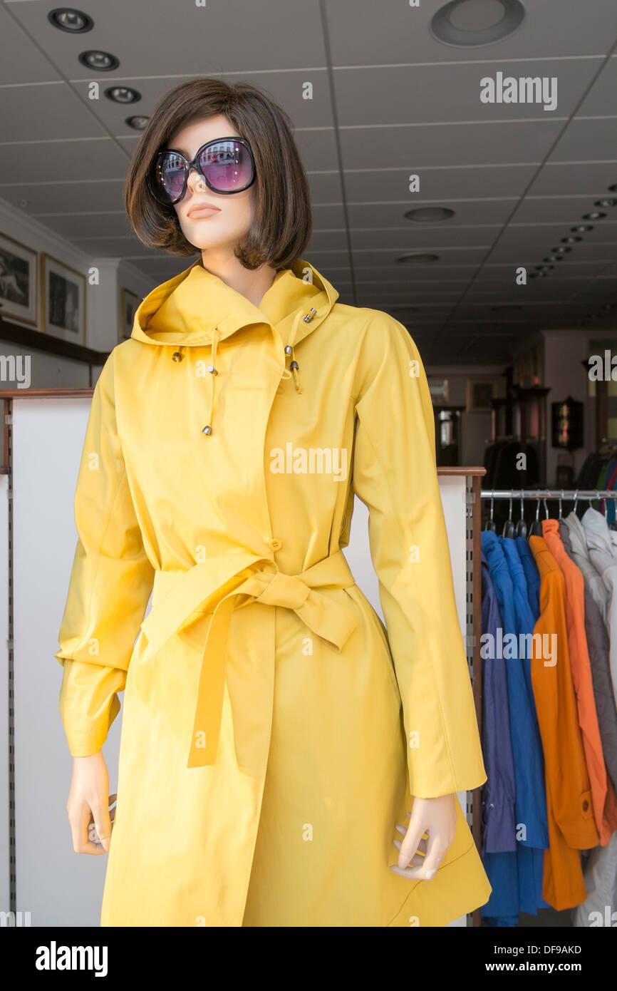 Shop window mannequin wearing yellow trench coat, Norway, Oslo - Stock Image