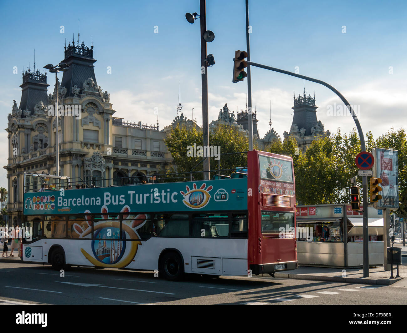 Tourist Bus in front of Old Port Authority Building in Port Vell area of Barcelona - Stock Image