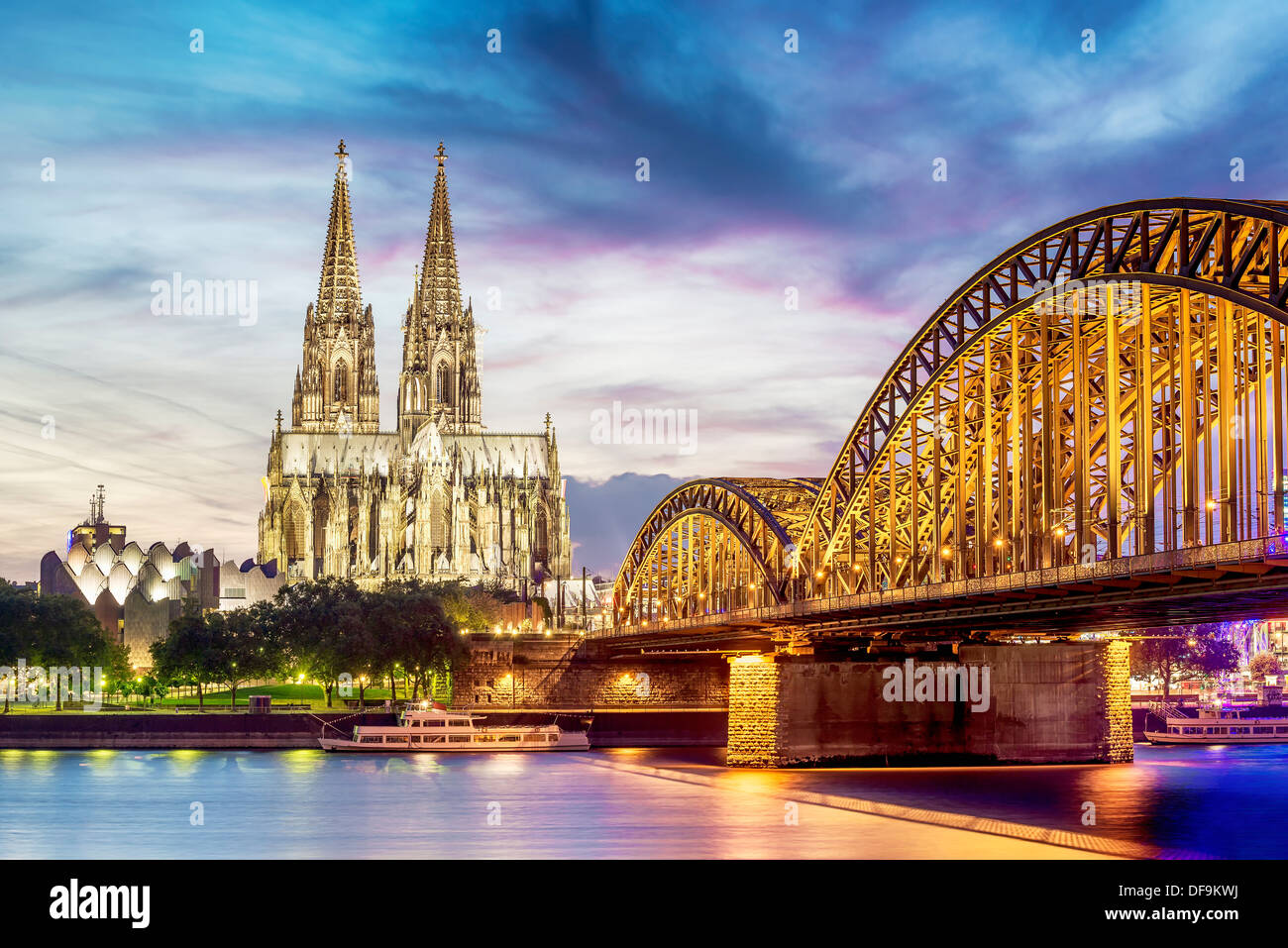 Illuminated Dom in Cologne with bridge and rhine at sunset - Stock Image