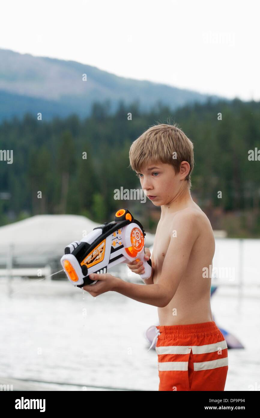 A twelve-year-old boy plays with a squirt gun - Stock Image