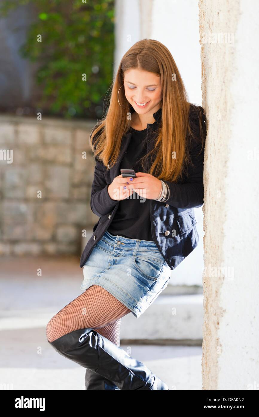 Attractive young woman is writting a message on a cellular phone - Stock Image