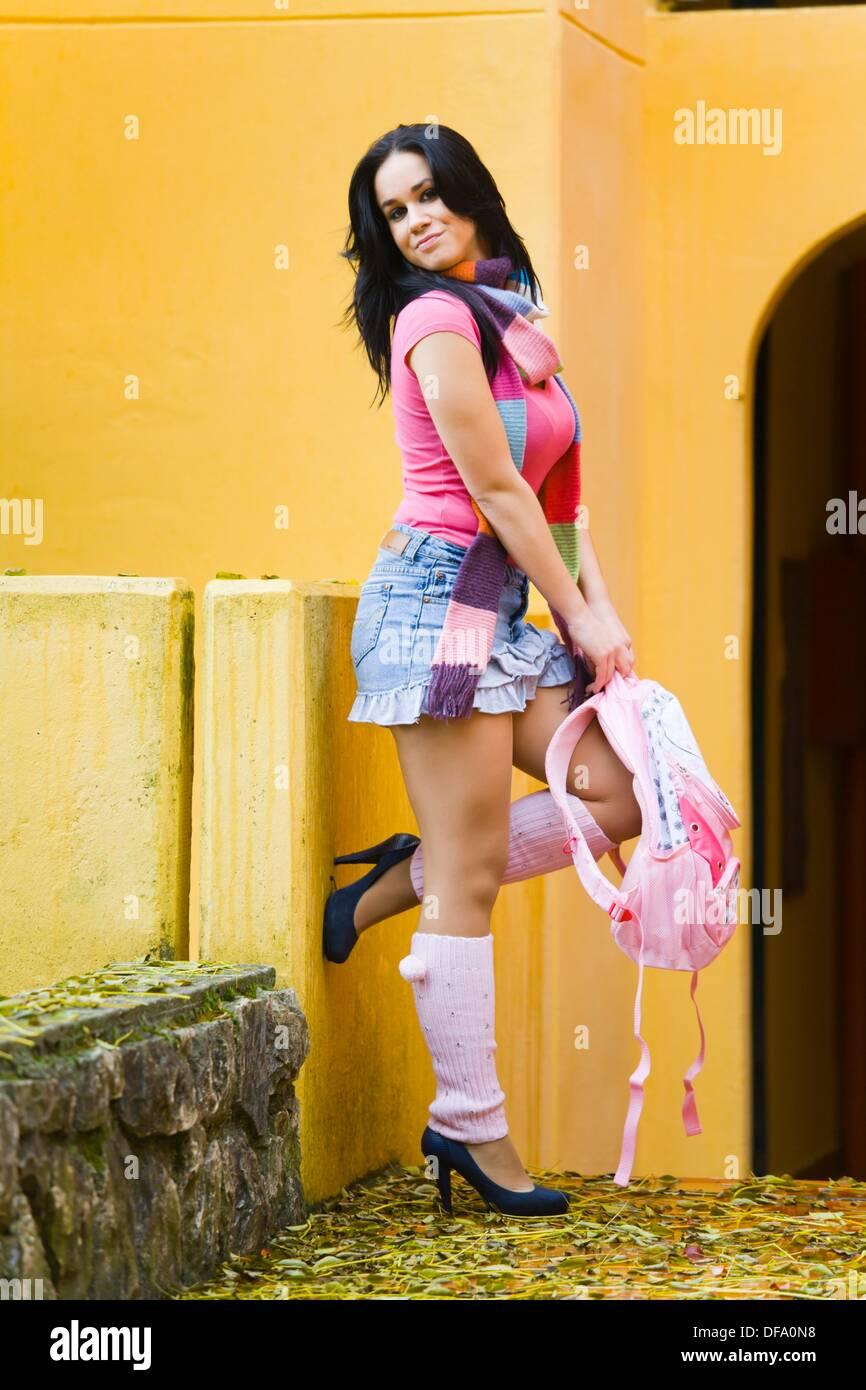 Attractive young schoolgirl in a short denim skirt - Stock Image
