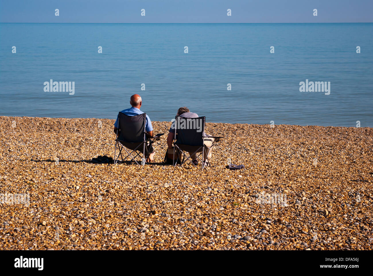 Rear View Of An Elderly Couple Sitting On Beach Chairs Looking Out To Sea Stock Photo