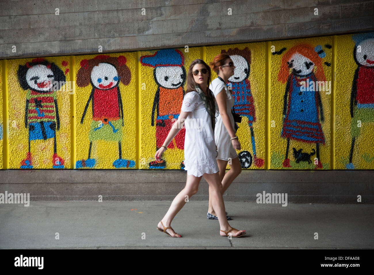 Street art graffiti piece showing characters growing up by artist Stik. on the South Bank, London, UK. - Stock Image
