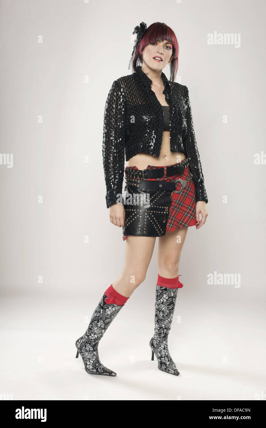 Redhaired rocker girl on boots and leather miniskirt looking  at the camera - Stock Image