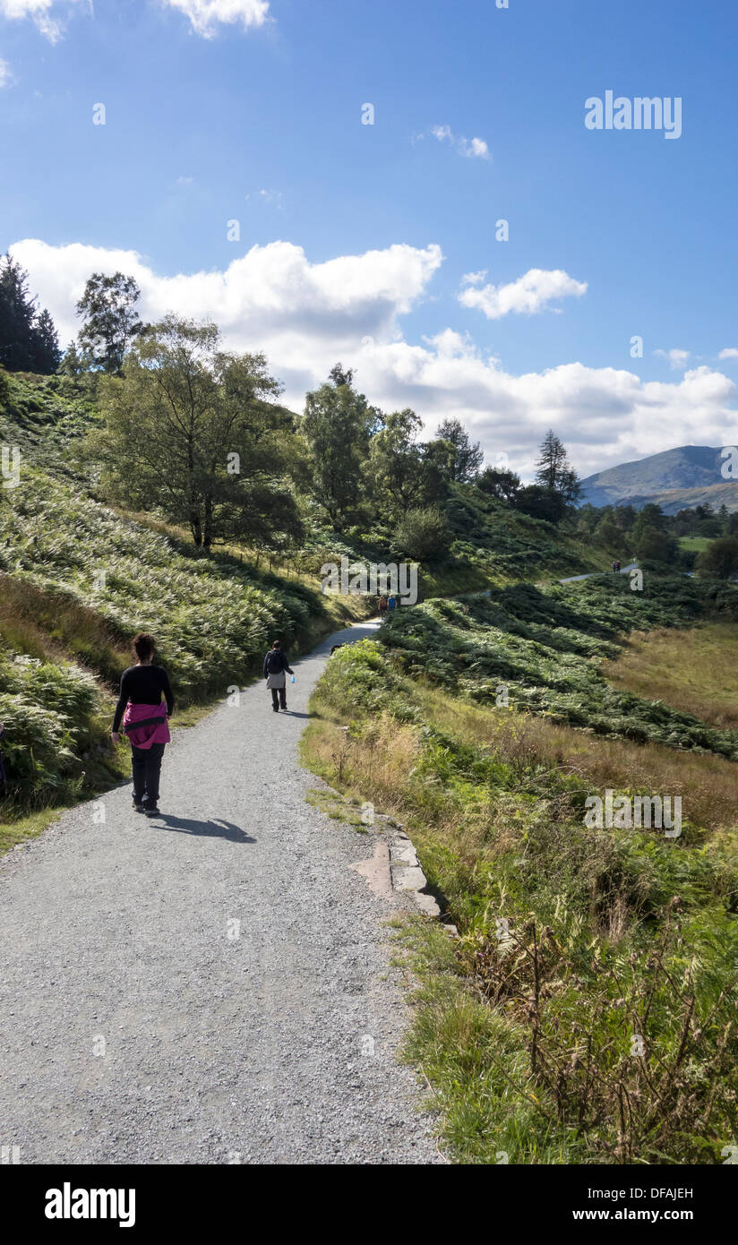 People walking along a gravel track, in the Lake District. - Stock Image