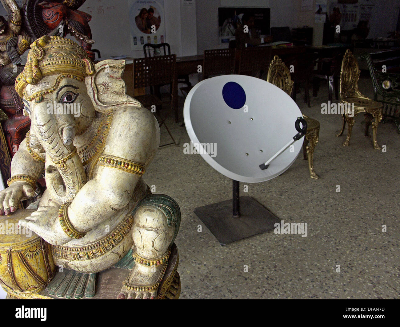 Satellite TV dish and Hindu deity (Ganesha) share floor space in a shop. Ooty. Tamil Nadu, India - Stock Image