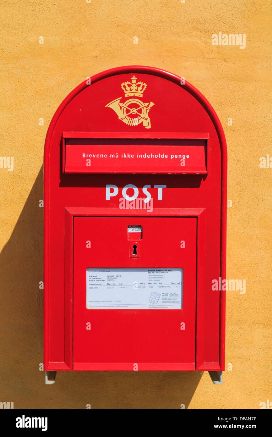 Danish red postbox on a yellow wall in Denmark, Scandinavia, Europe - Stock Image