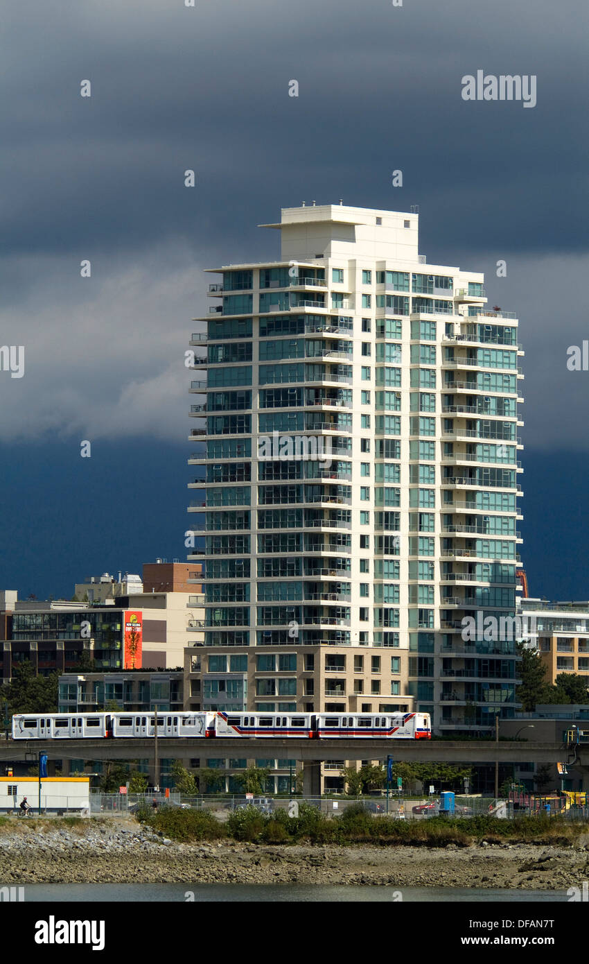 The Skytrain passes below an apartment tower at the east end of False Creek, Vancouver, BC, Canada Stock Photo