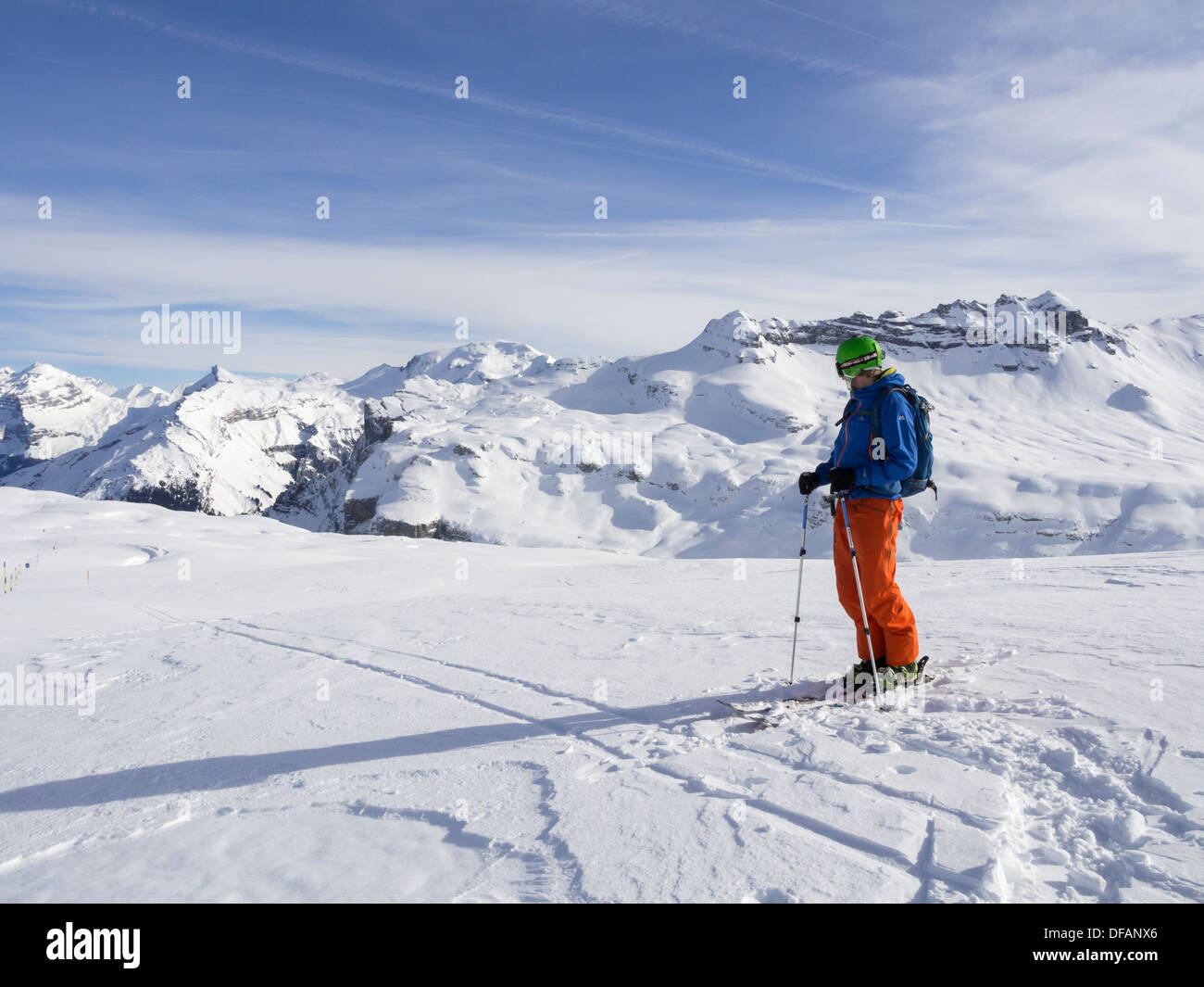 Male skier skiing in Le Grand Massif ski area looking at snowcapped mountains in the French Alps. Flaine, Rhone Stock Photo
