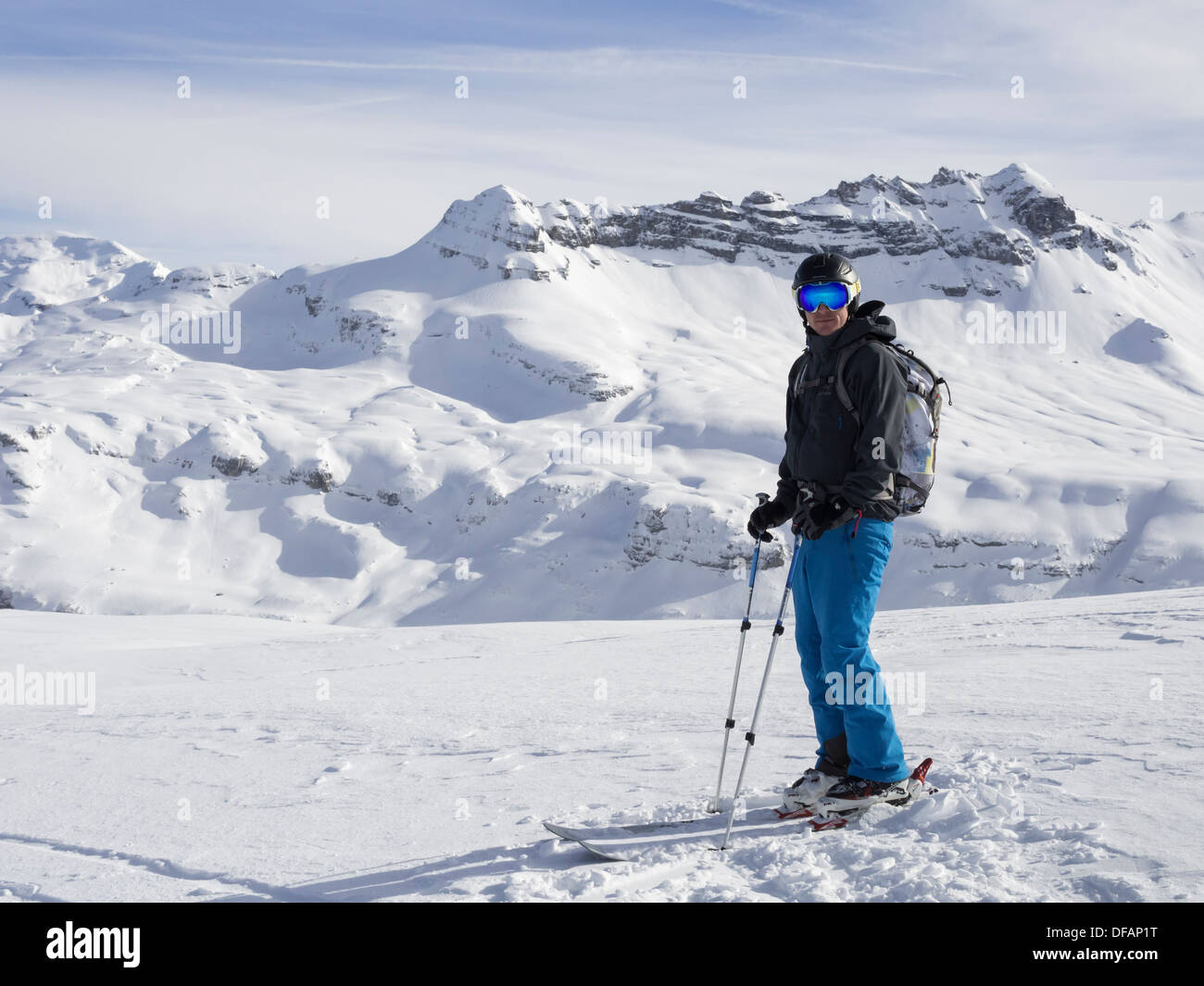 Male skier skiing in Le Grand Massif ski area with views to snowcapped mountains in the French Alps. Flaine, Rhone Stock Photo